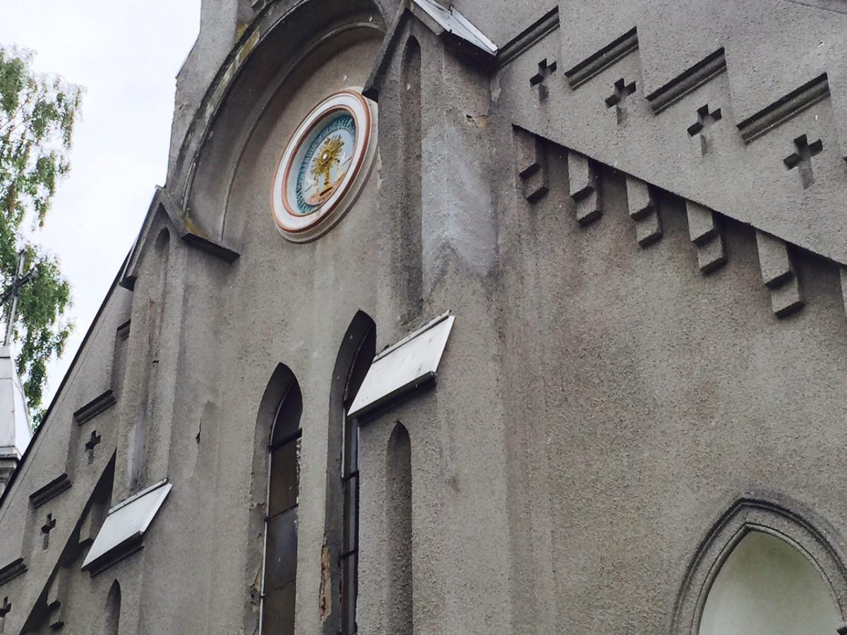 Medalion mariawicki nad wejściem do kościoła p.w. Podwyższenia Krzyża Świętego w Grzmiącej